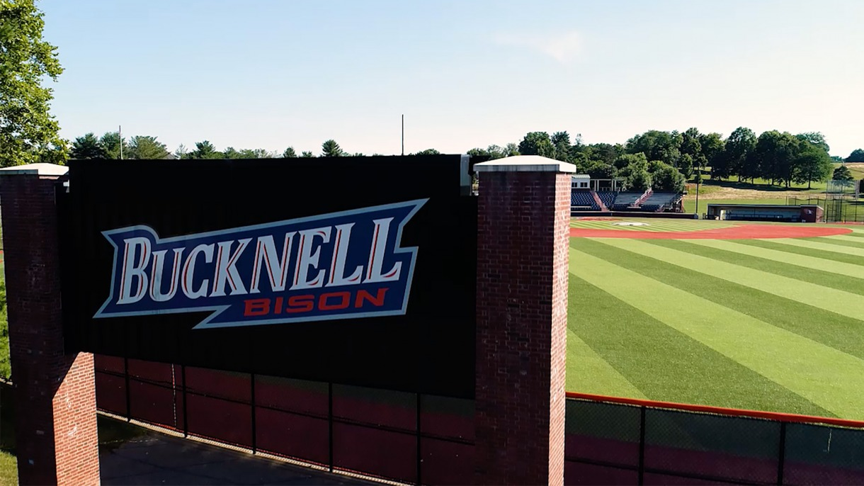 Bucknell logo on wall behind baseball field.
