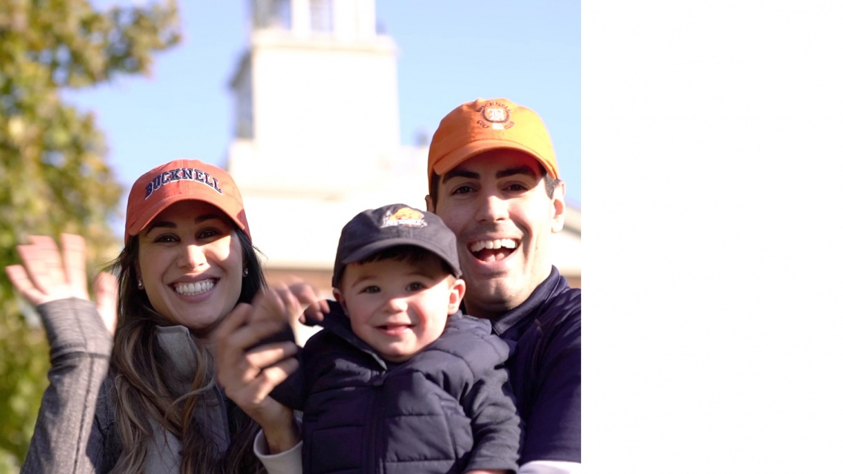 A Bucknell family smiling and waving.