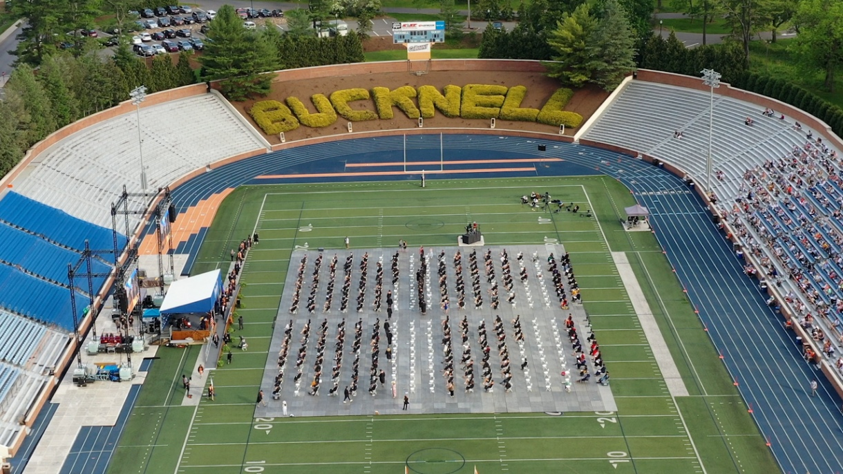 An aerial view of Christy Mathewson-Memorial Stadium during Commencement 2021. Graduates sit on the field in chairs facing a stage.