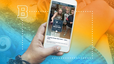 A woman's hand holds a smartphone with a Bucknell custom viewbook displayed on screen