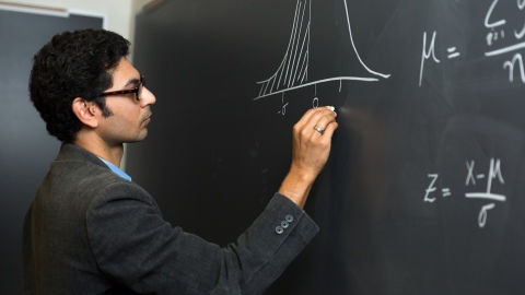 Professor Owais Gilani draws on chalkboard