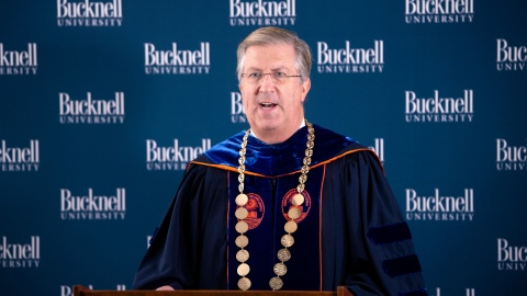 President John Bravman speaks at podium dressed in regalia