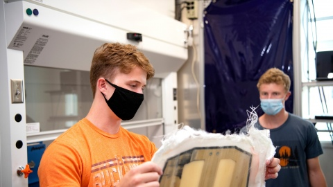 Two male students in masks work in an engineering lab