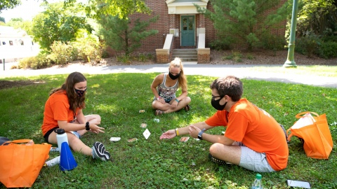 Three students in masks sit in a circle on the grass during move-in
