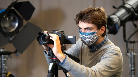 Student with camera in media studio