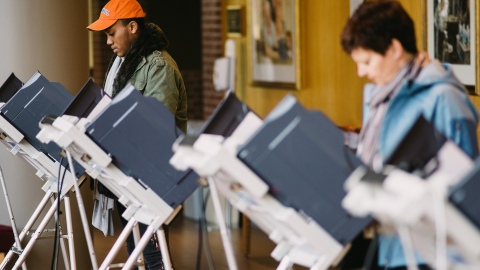 Students cast ballots at voting machines.