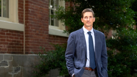 Professor Matt Bailey, in a blue jacket and tie, stands beside a brick building on Bucknell's campus