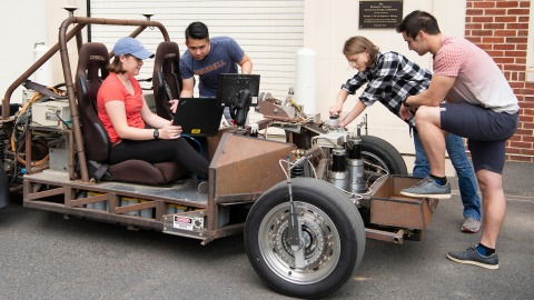Engineering students work on electric car