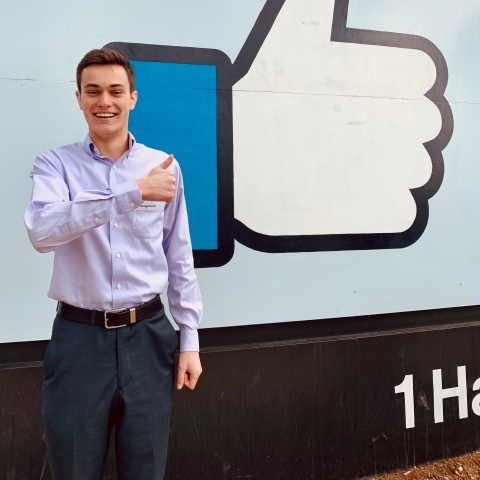 Ryan Bailis in front of Facebook sign.