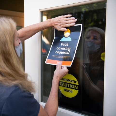 A library worker posts a sign on a door reminding visitors to wear face coverings.