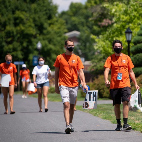 students in masks and orange t-shirts walk in front of Rooke Science Center