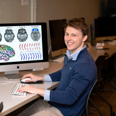 Will Snyder '21 sits at desk with computers displaying brain scans