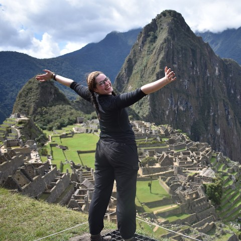 Student standing above Machu Picchu with arms outstretched