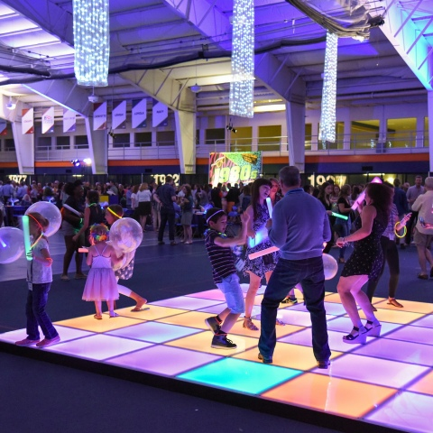 People dancing on a light up dance floor