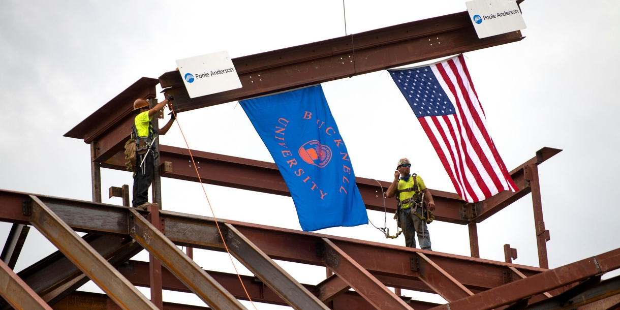 Two construction workers guide a beam into place on top of the building. American and Bucknell University flags hang from the beam.
