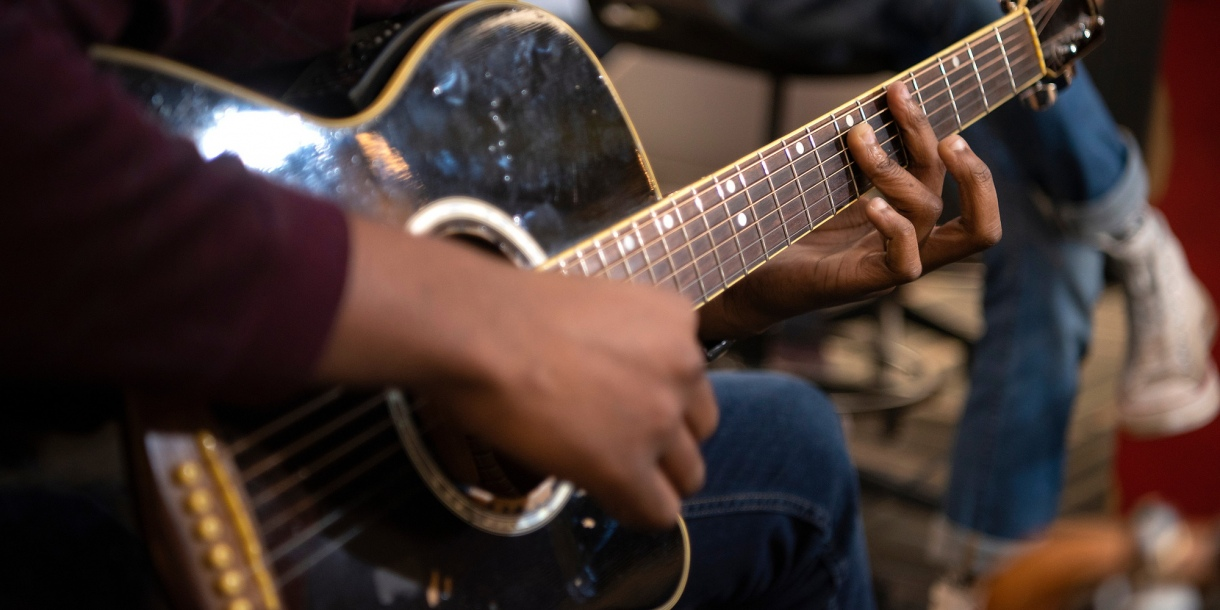 Detail of student playing acoustic guitar