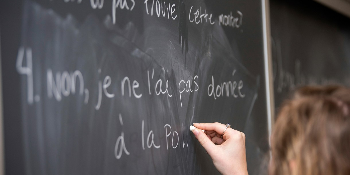 Student writing on the board in French class
