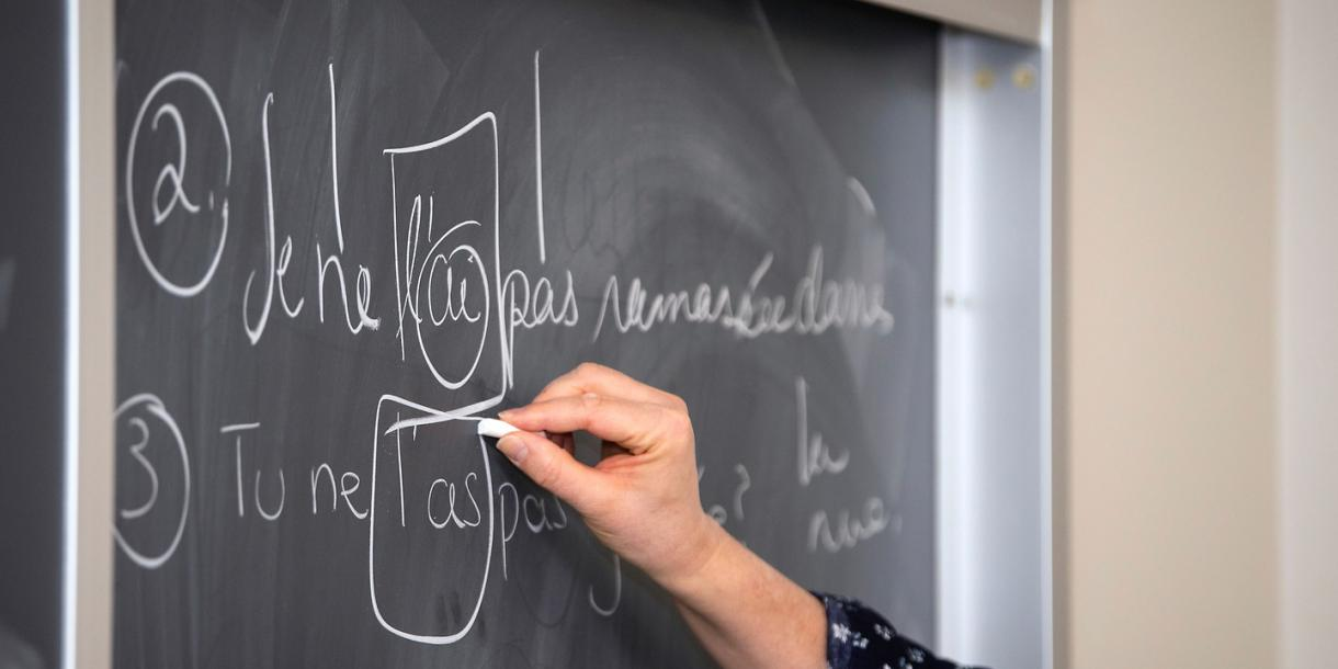 Professor writing French on chalkboard.
