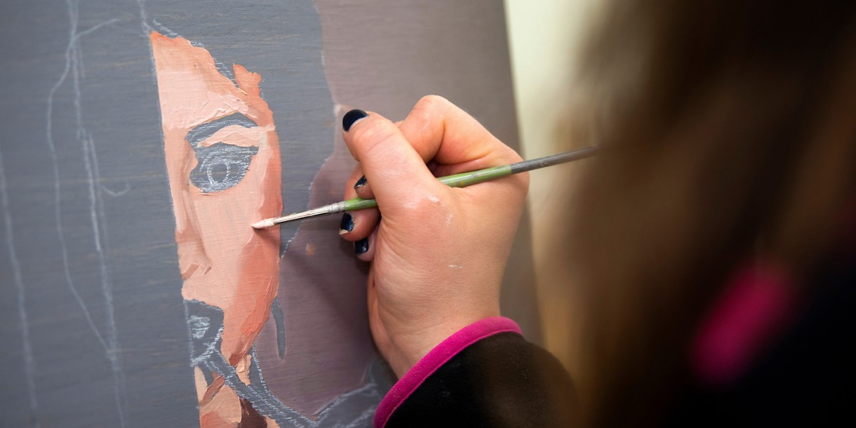 A painter meticulously creating a face on canvas