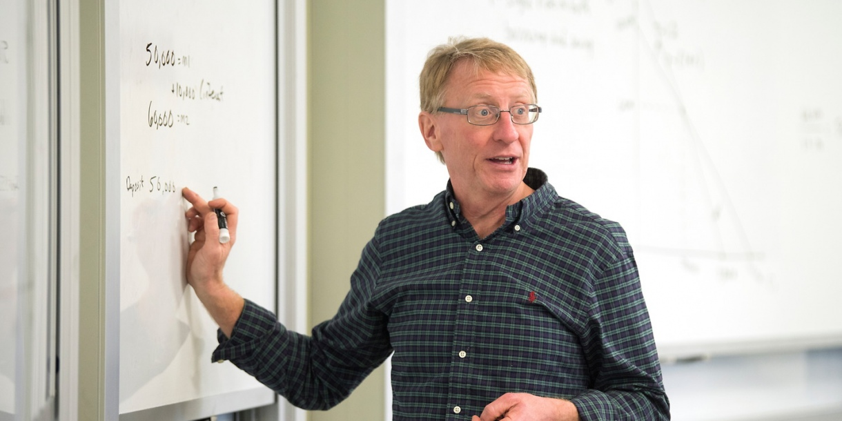 Professor Kinnaman pointing at a whiteboard