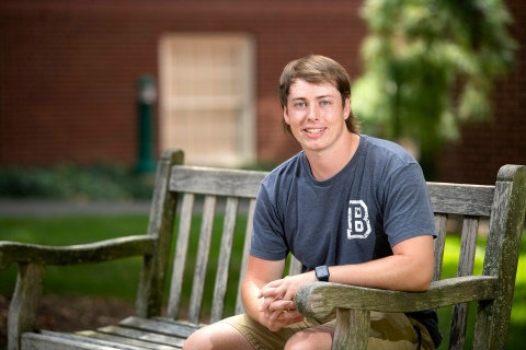 Portrait of Jonathan Hayes '21 sitting on bench