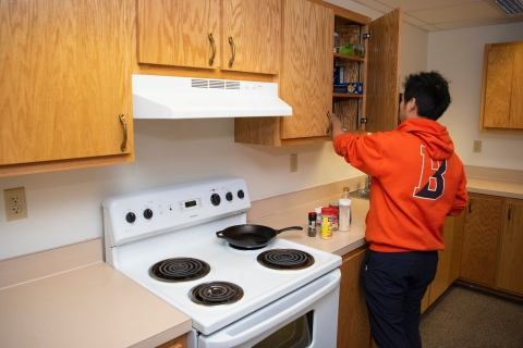 Student using the Vedder Hall kitchen