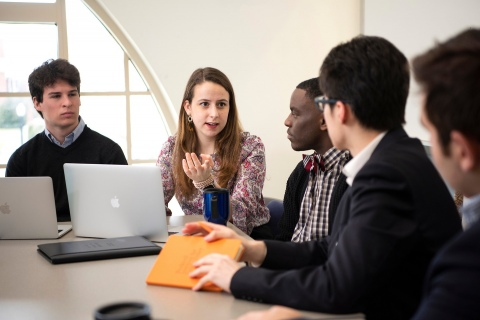 Students discuss around a conference table