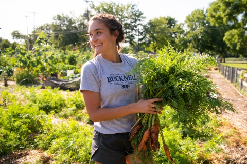 Student with bundle of carrots in Community Garden