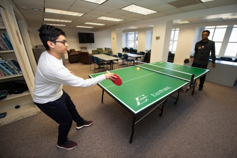Students playing ping pong in common room