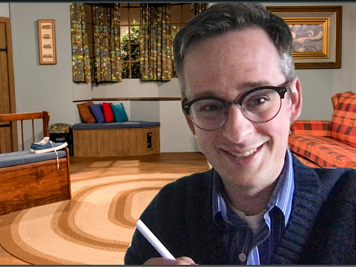 Evan Peck in a Zoom meeting with the Mr. Rogers' Neighborhood home background behind him.