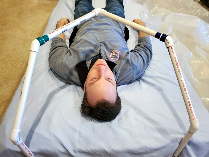 Professor Brandon Vogel lies under the frame of a prototype intubation tent.