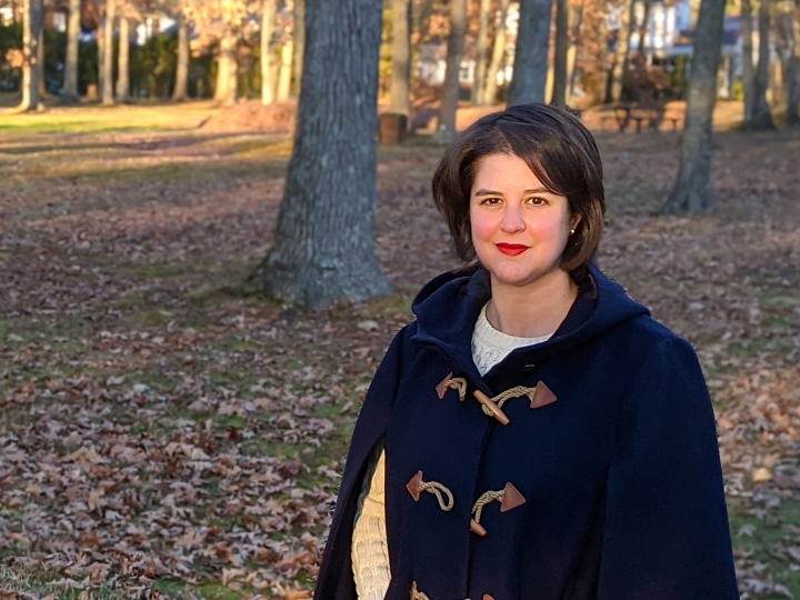 Casey Barber poses before a field of trees and fallen leaves.
