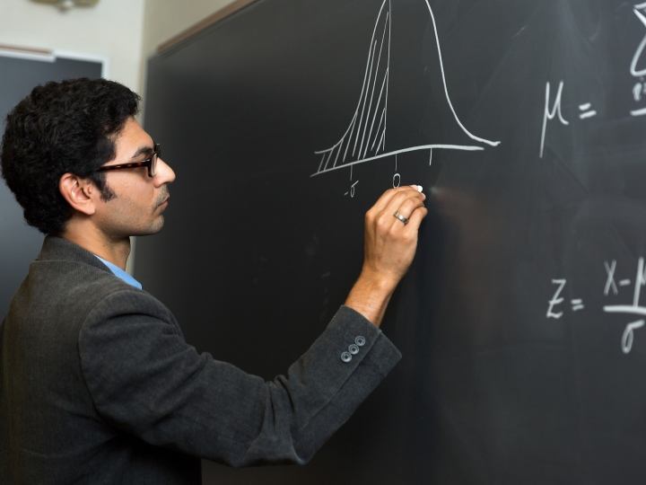 Professor Owais Gilani draws on chalkboard