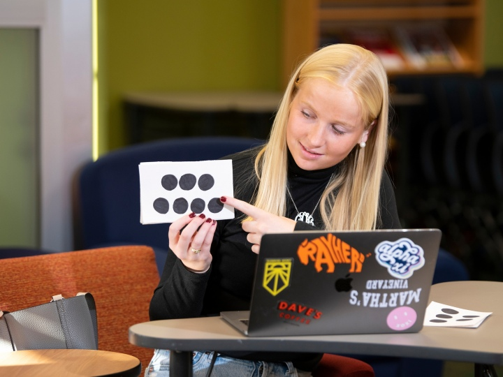 Cara O'Neill points to a flashcard while tutoring elementary school students online