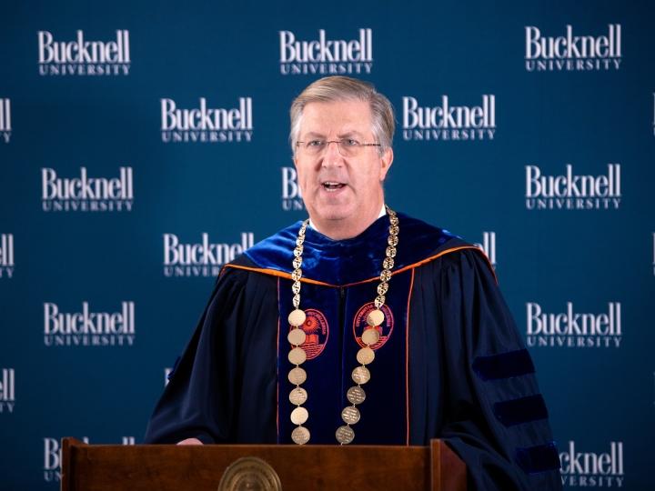 President John Bravman speaks at podium dressed in regalia