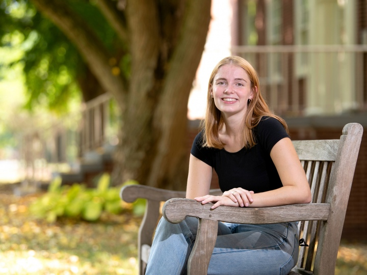 Ella sits on a bench on campus