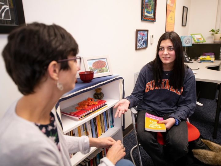 Professor Elena Machado and Emily Sanchez '23 talk in a faculty office, Sanchez holding a book