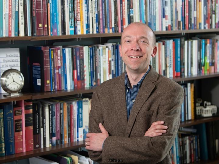 Scott Meinke poses for portrait in front of bookshelf