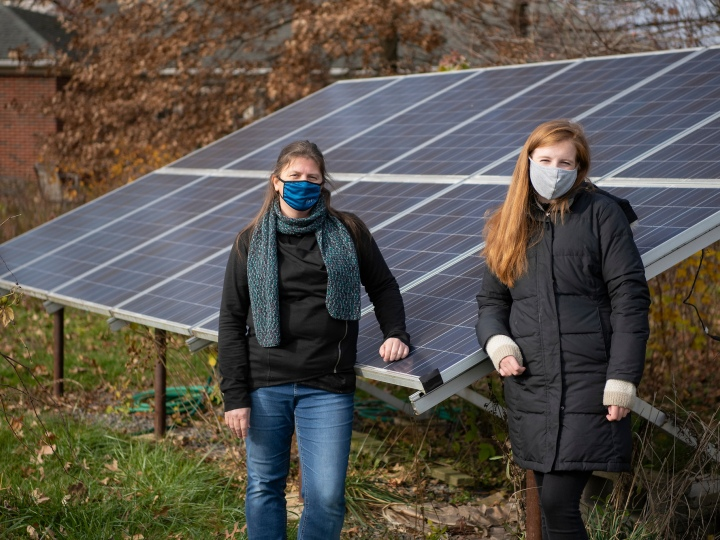 Shaunna Barnhart and Maggie Barton '21 stand by solar panels