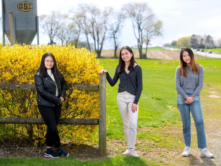Student researchers pose at farm