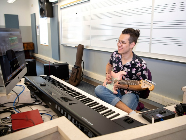 Ian Herdt plays a guitar in front of a musical keyboard and computer